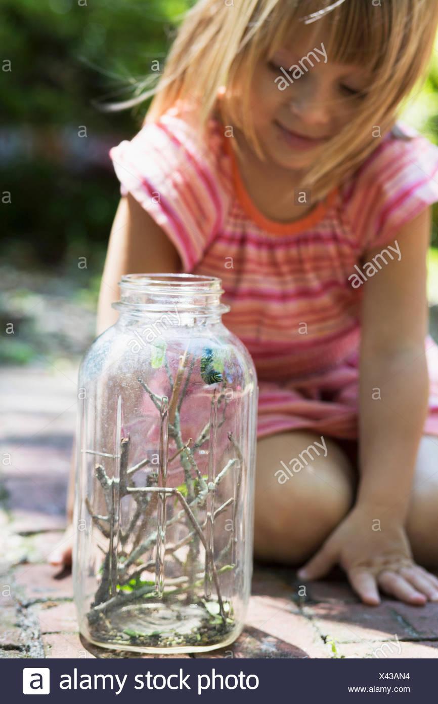 Girl kneeling to watch caterpillar jar in garden Stock Photo