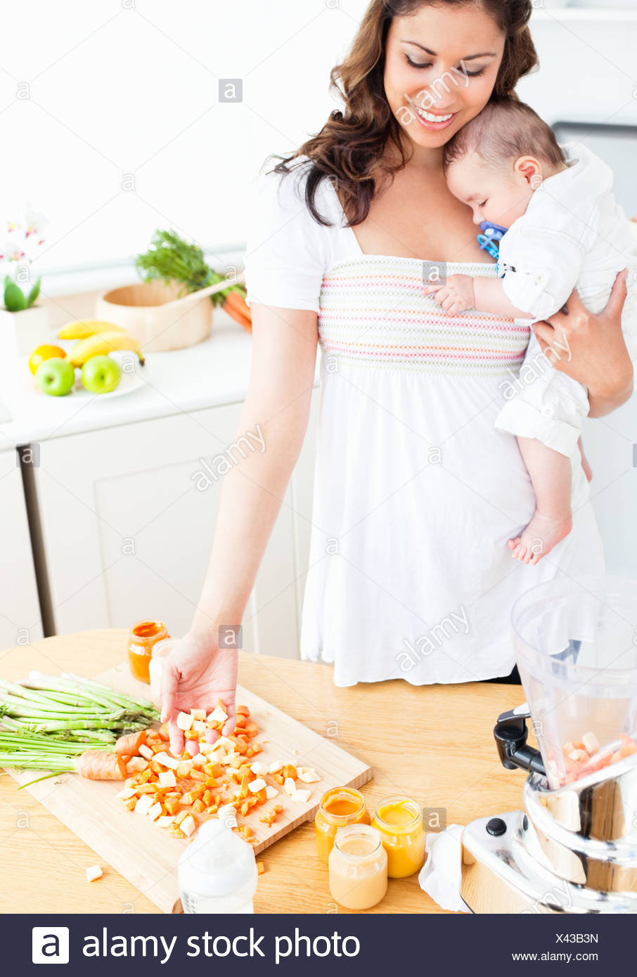 Radiant mother preparing food for her adorable baby in the kitchen - Stock Image