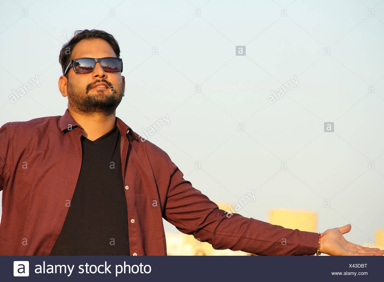 Young Indian man with goggles and outstretched hands as a welcome gesture Stock Photo