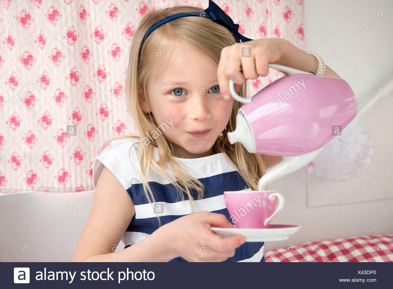 Portrait of young girl pouring tea in caravan - Stock Image