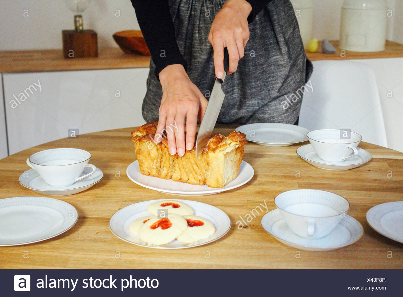 Woman Cutting Bread On Table - Stock Image