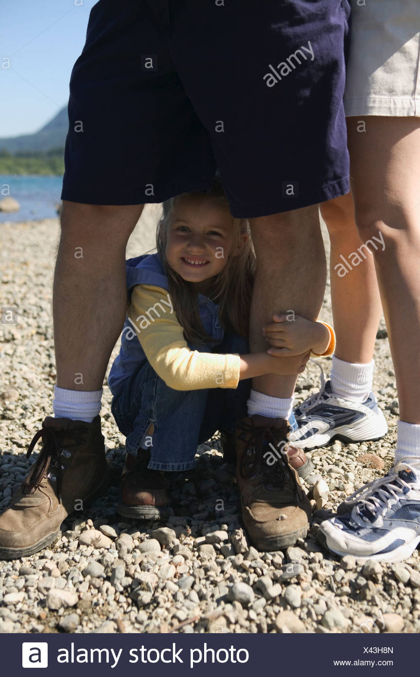 Young girl crouched between dad s legs - Stock Image