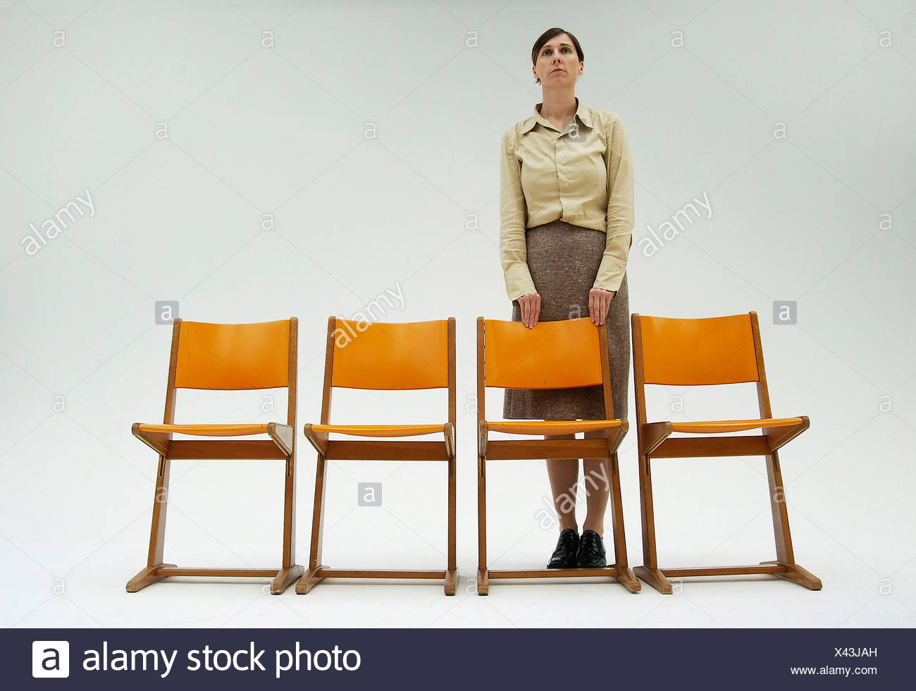 Woman wearing conservative clothes standing behind a row of orange chairs - Stock Image