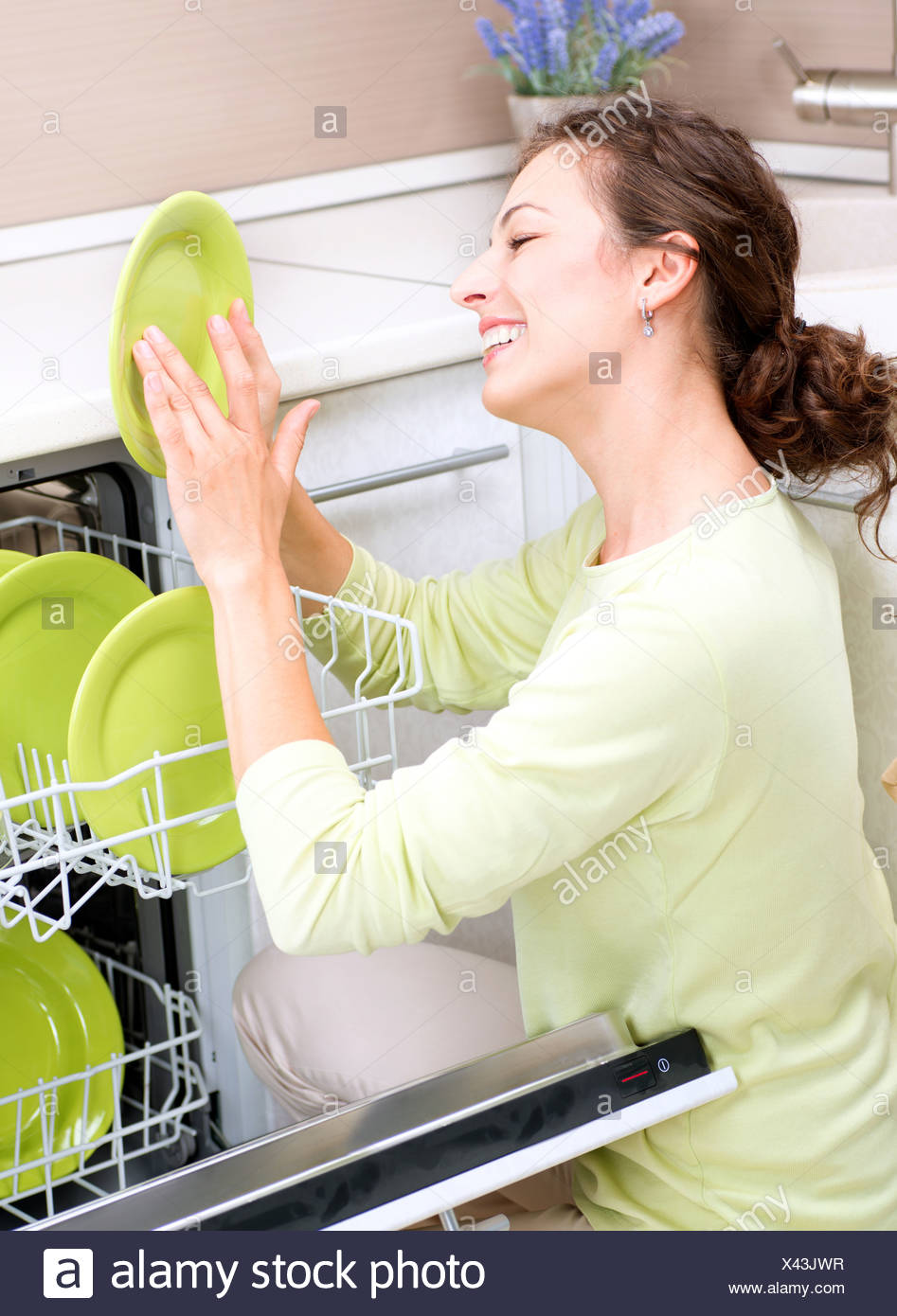 Dishwasher. Young woman in the Kitchen doing Housework. Wash-up - Stock Image