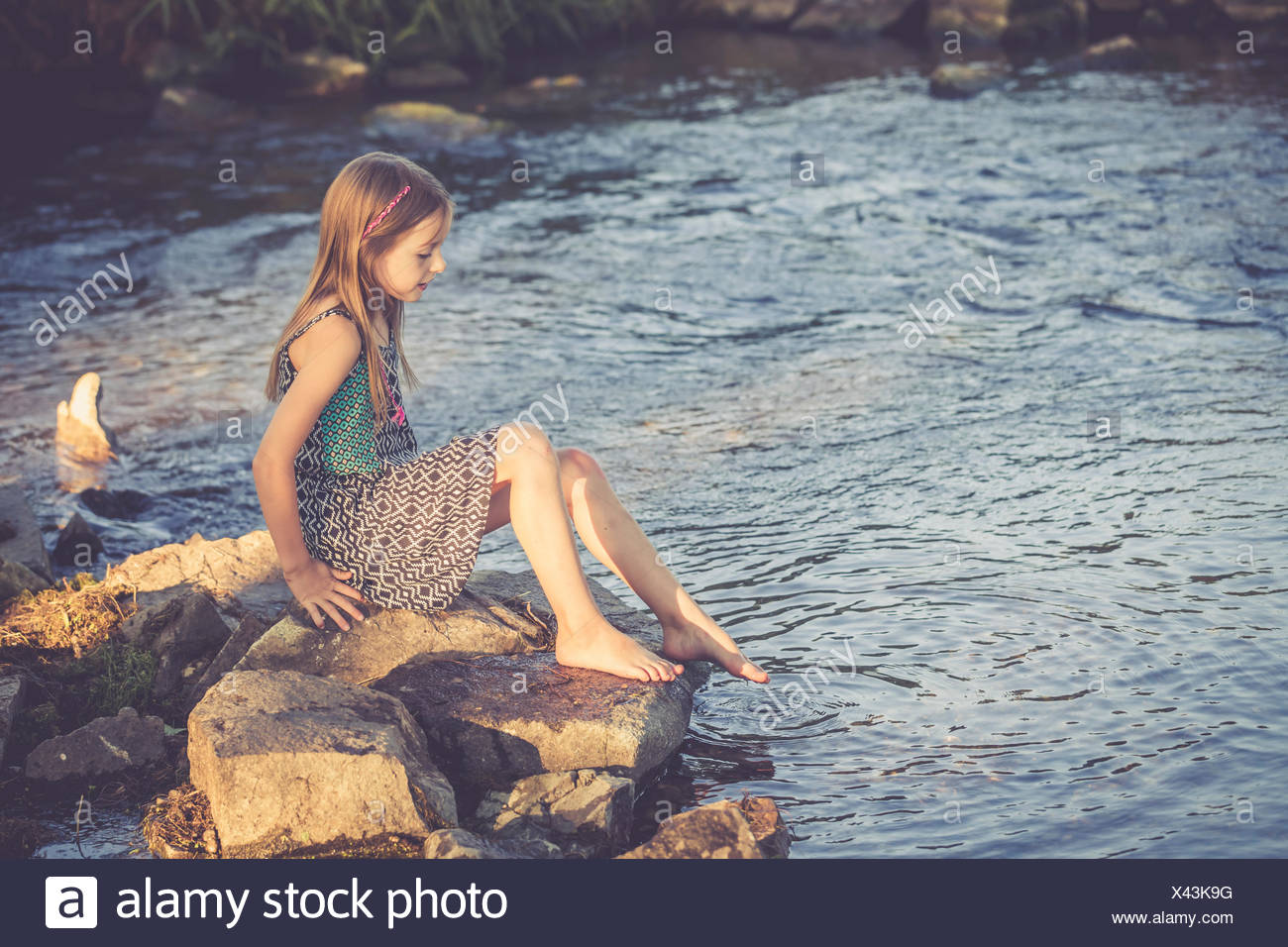Girl sitting at waterside checking temperature of the water - Stock Image