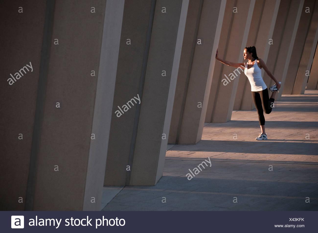 Runner stretching on concrete pillar - Stock Image