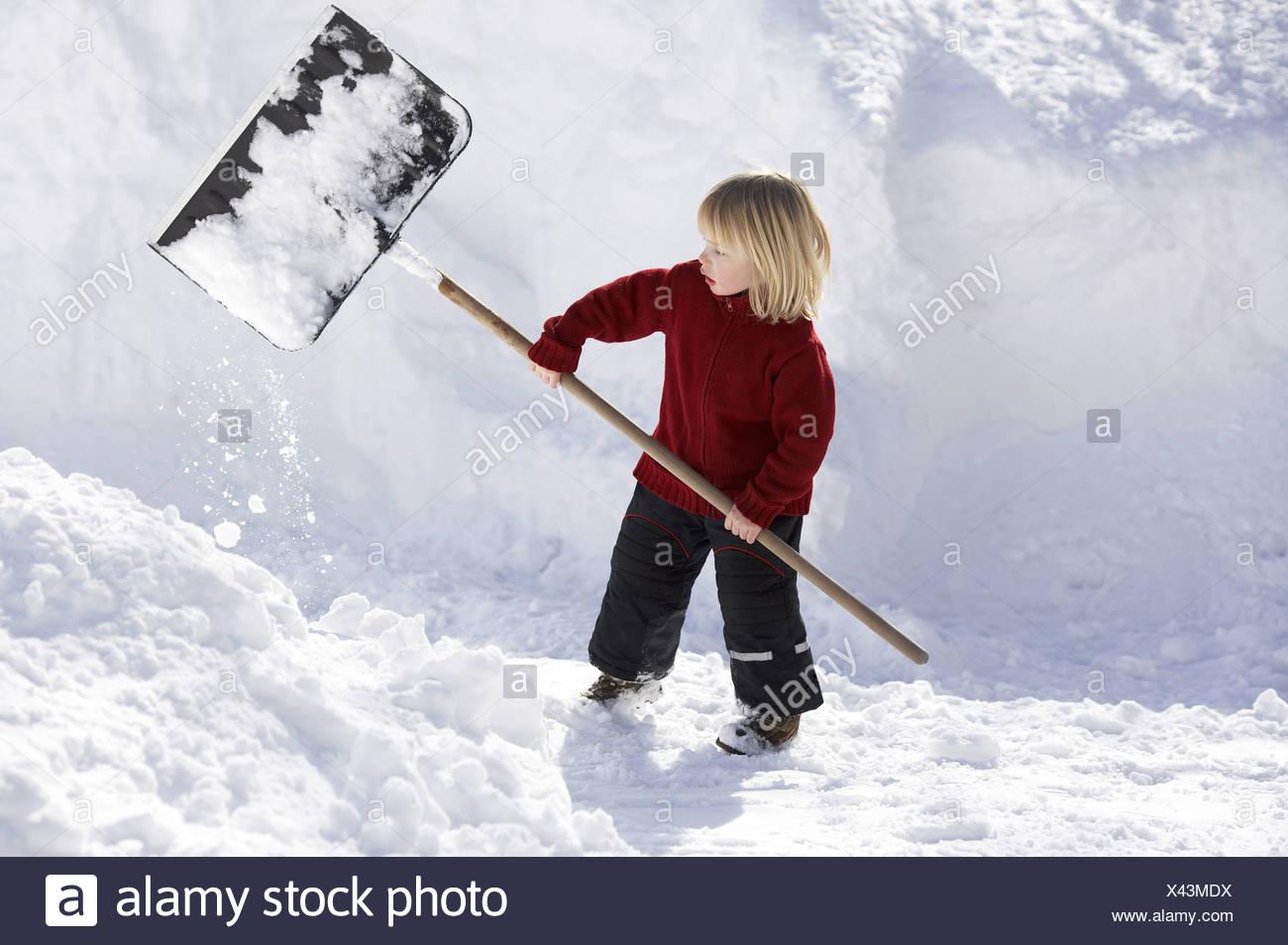 Give birth winter-clothing snow-shovels 4 years child blond ski-pants snow-shovel shovel holds shovels snow-evacuates plays - Stock Image