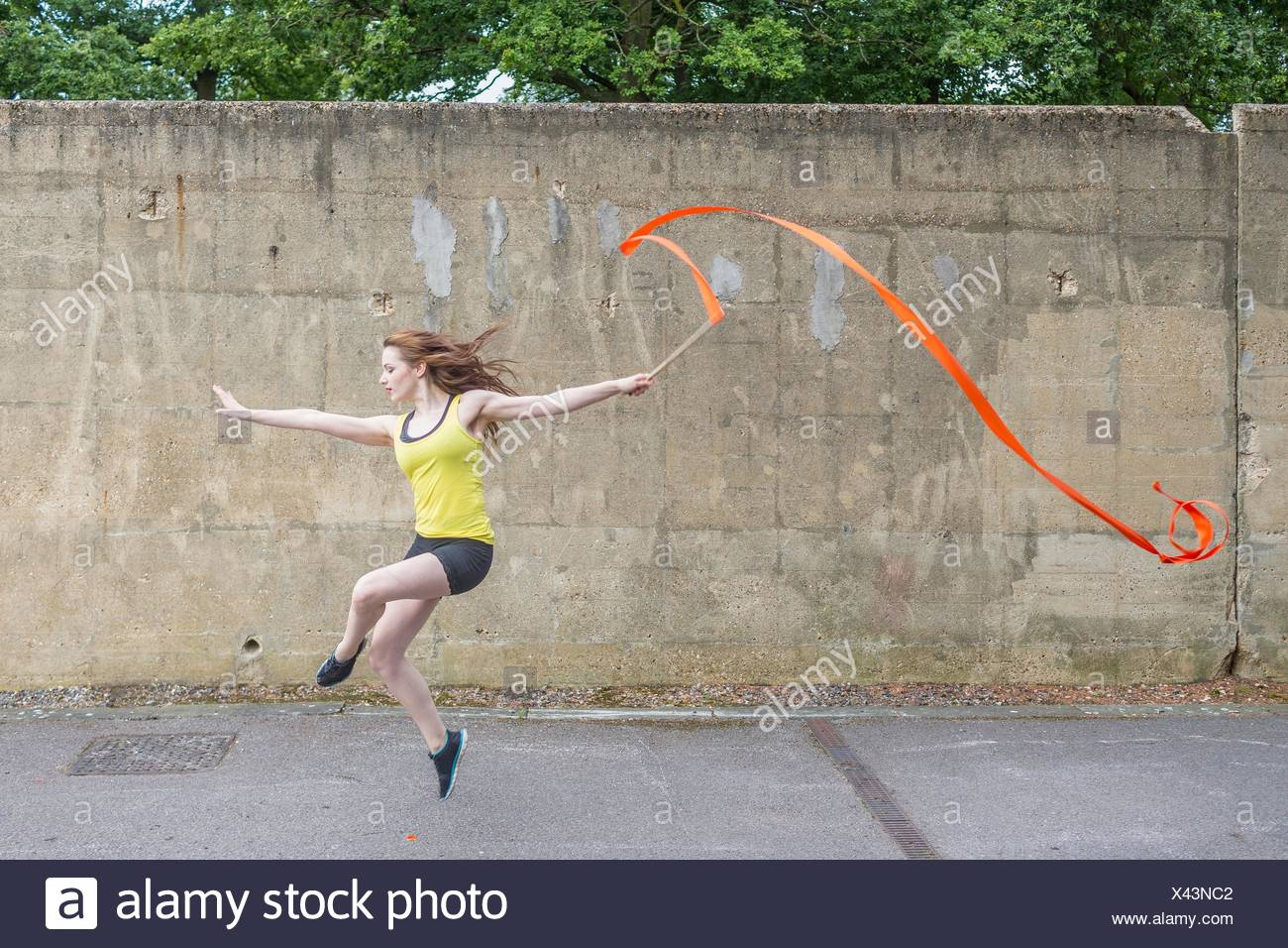 Young woman practising ribbon dance on court - Stock Image