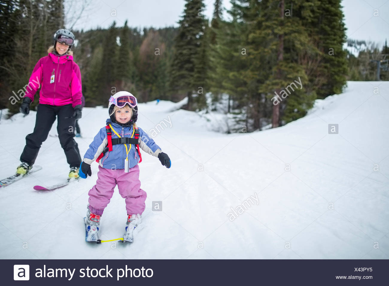 Little girl (2-3) learning skiing with mother - Stock Image