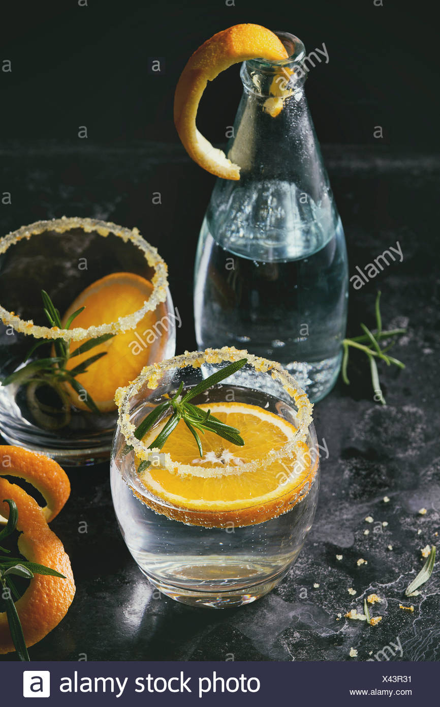 Tonic water cocktail with rosemary and orange. Two glasses and bottle with zest sugar and bubbles over black texture background. Refreshing beverage a - Stock Image