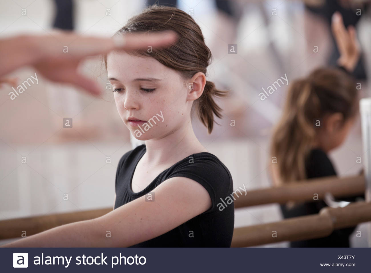Ballet school girls practicing ballet position at the barre - Stock Image