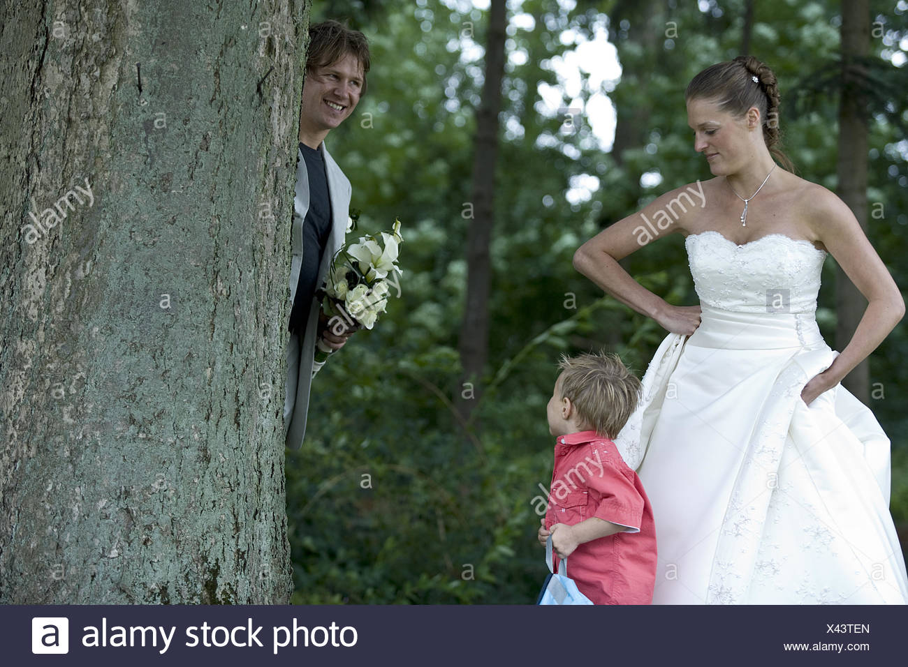 Groom playing hide and seek with his son - Stock Image