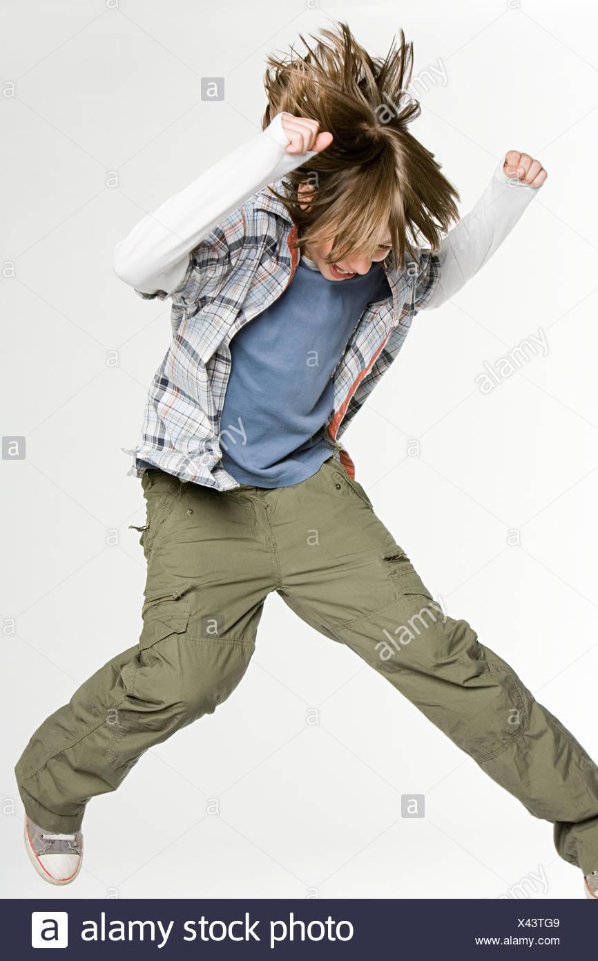 A teenage boy jumping - Stock Image