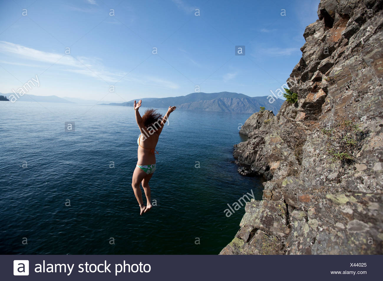 Female jumping off small cliff into a lake in Idaho. - Stock Image