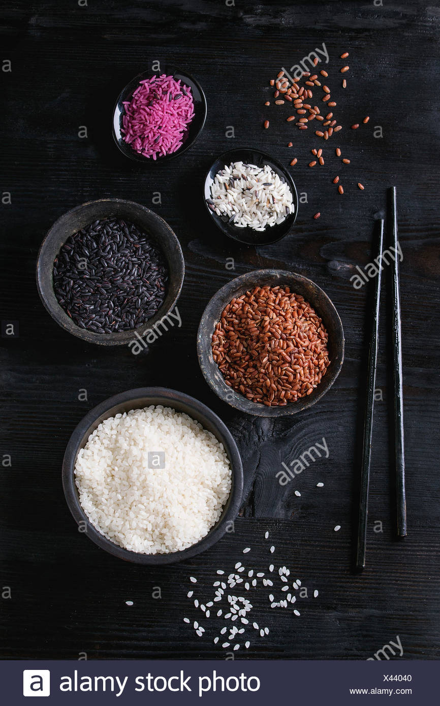 Variety assortment of raw uncooked colorful rice white, black, brown, pink in black bowls over burnt wooden background with chopsticks. Top view with  - Stock Image