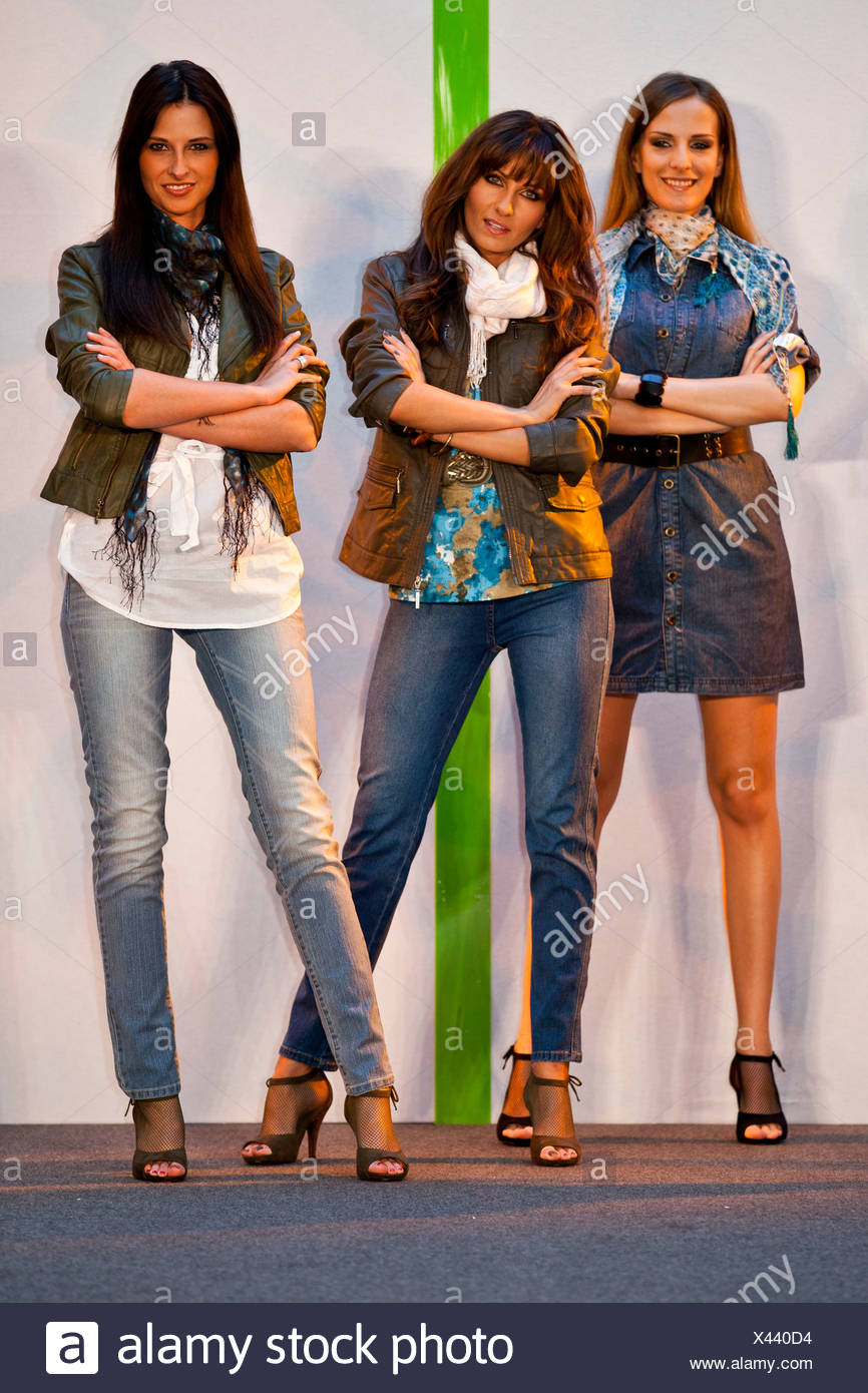 Three models confidently standing on a stage Stock Photo