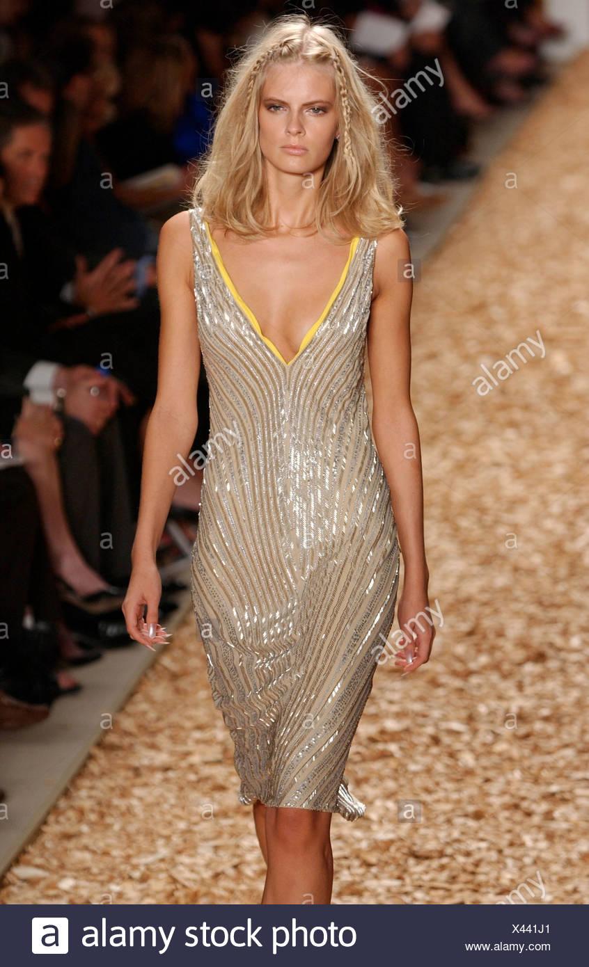 Anne Klein Ready to Wear New York spring summer fashion show Model blonde hair plaits wearing beige shiny dress yellow trim Stock Photo