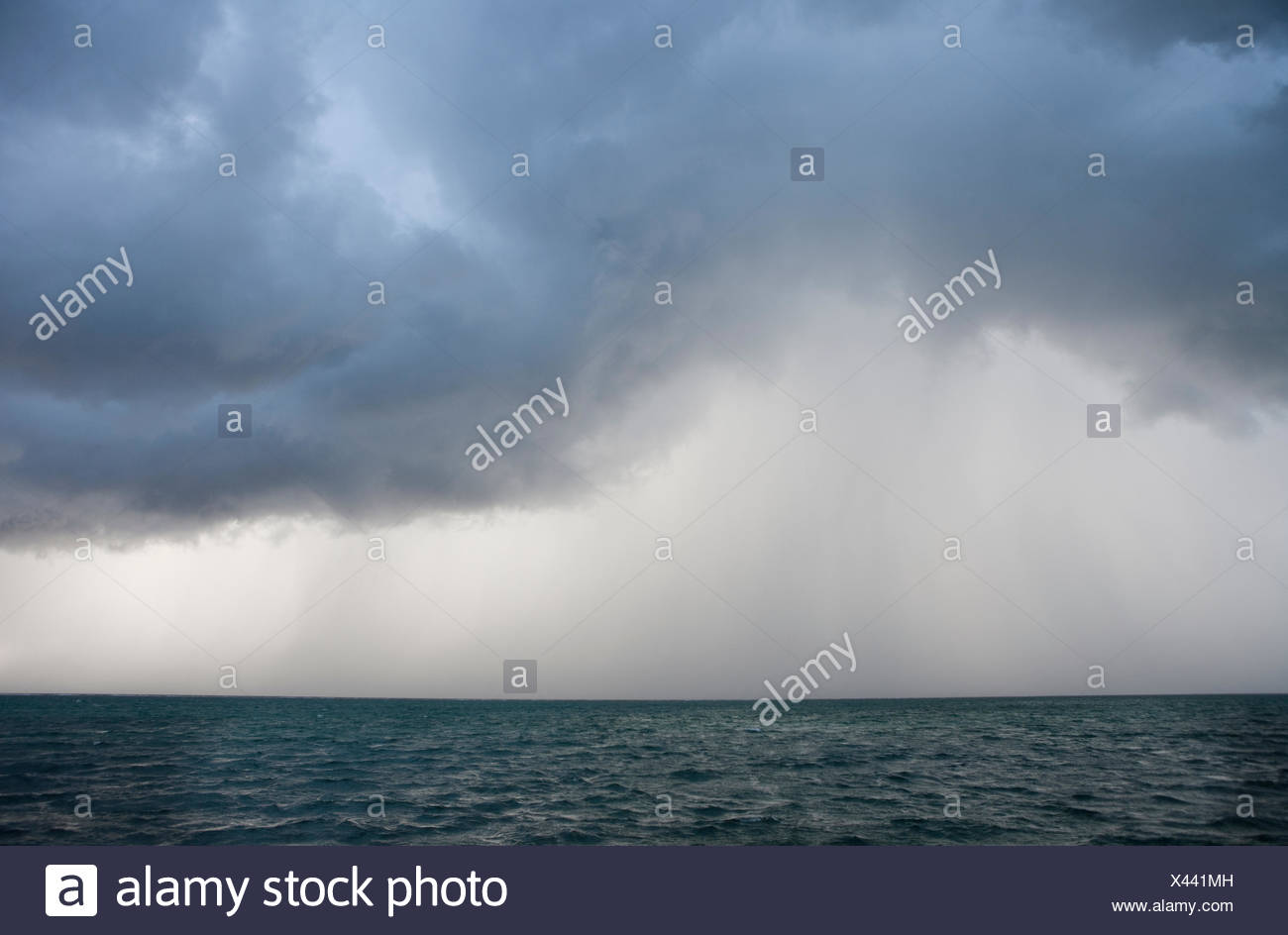 a view of an ocean storm with menacing clouds and rain showering below - Stock Image