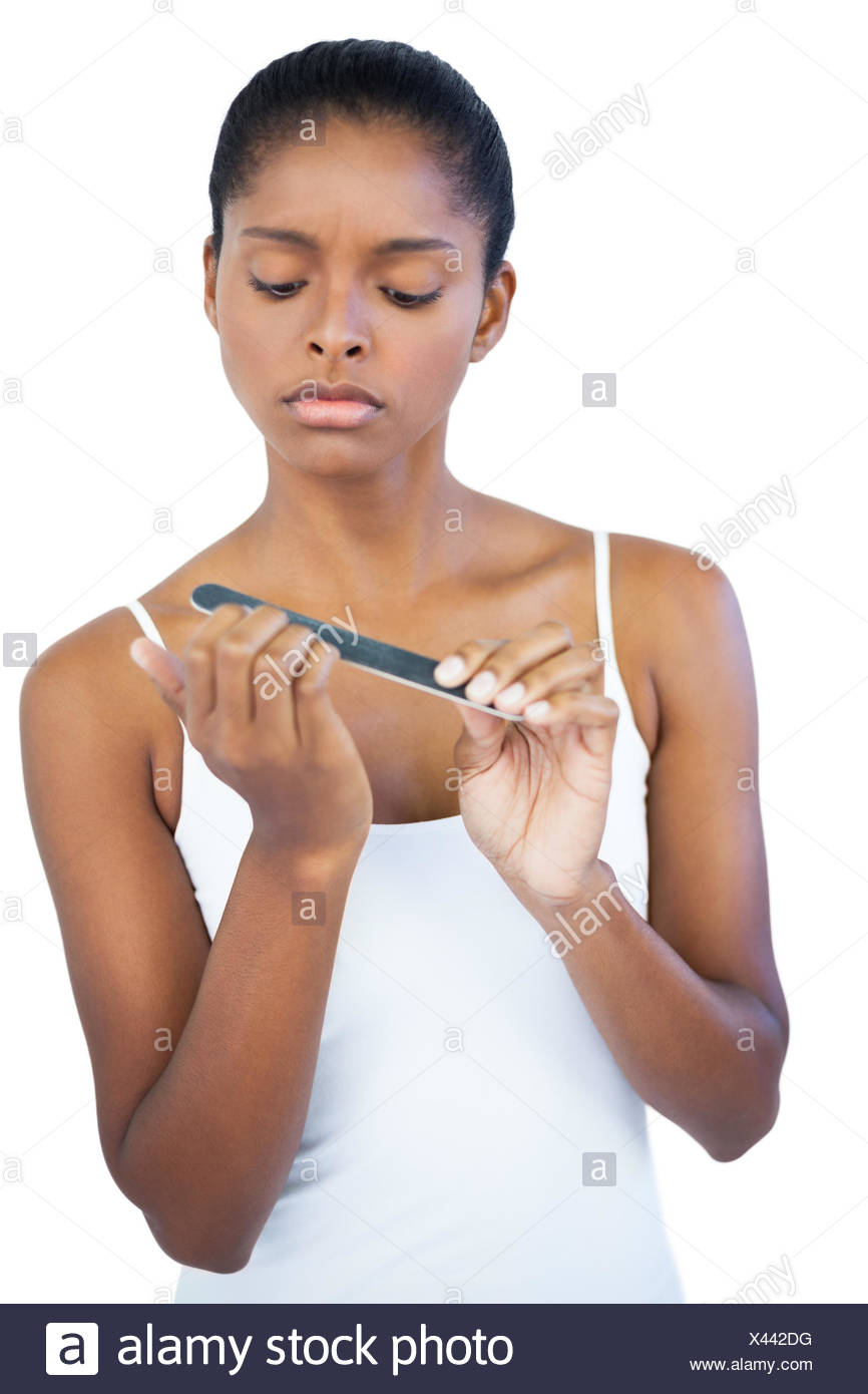 Serious woman using nail file on white background Stock Photo