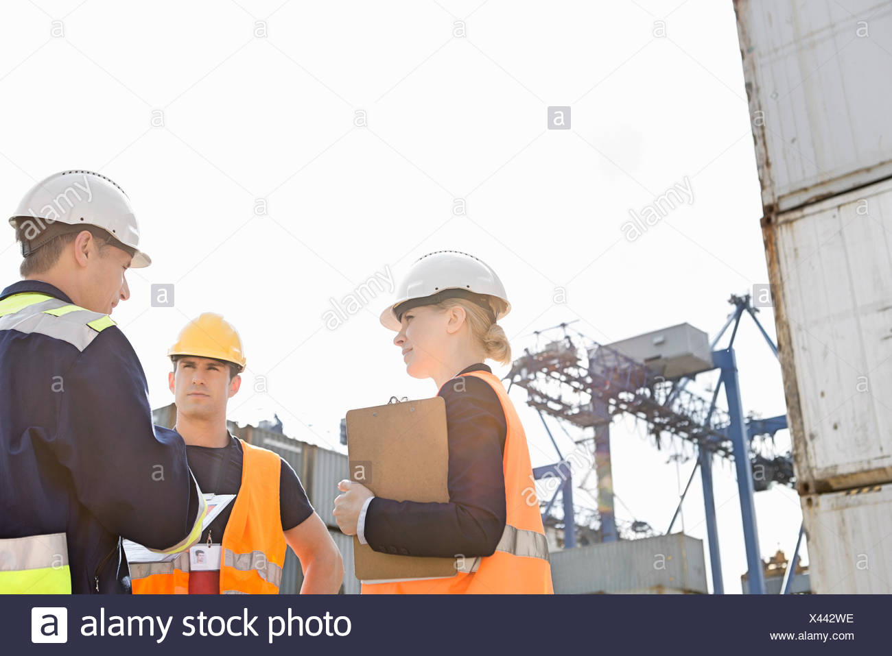 Workers discussing in shipping yard - Stock Image