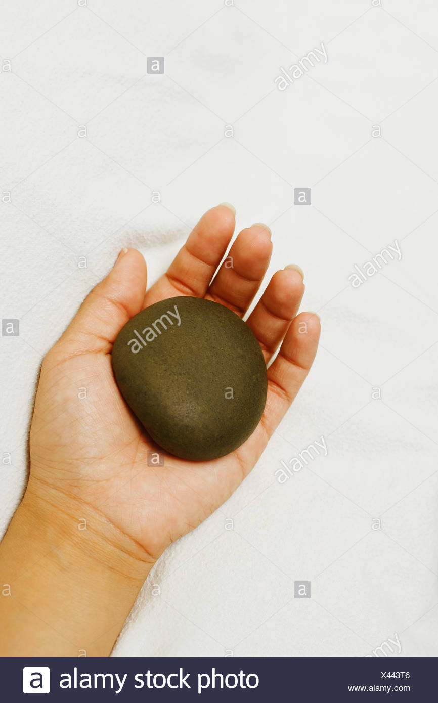 Close-up of a person's hand holding a spa hot stone - Stock Image