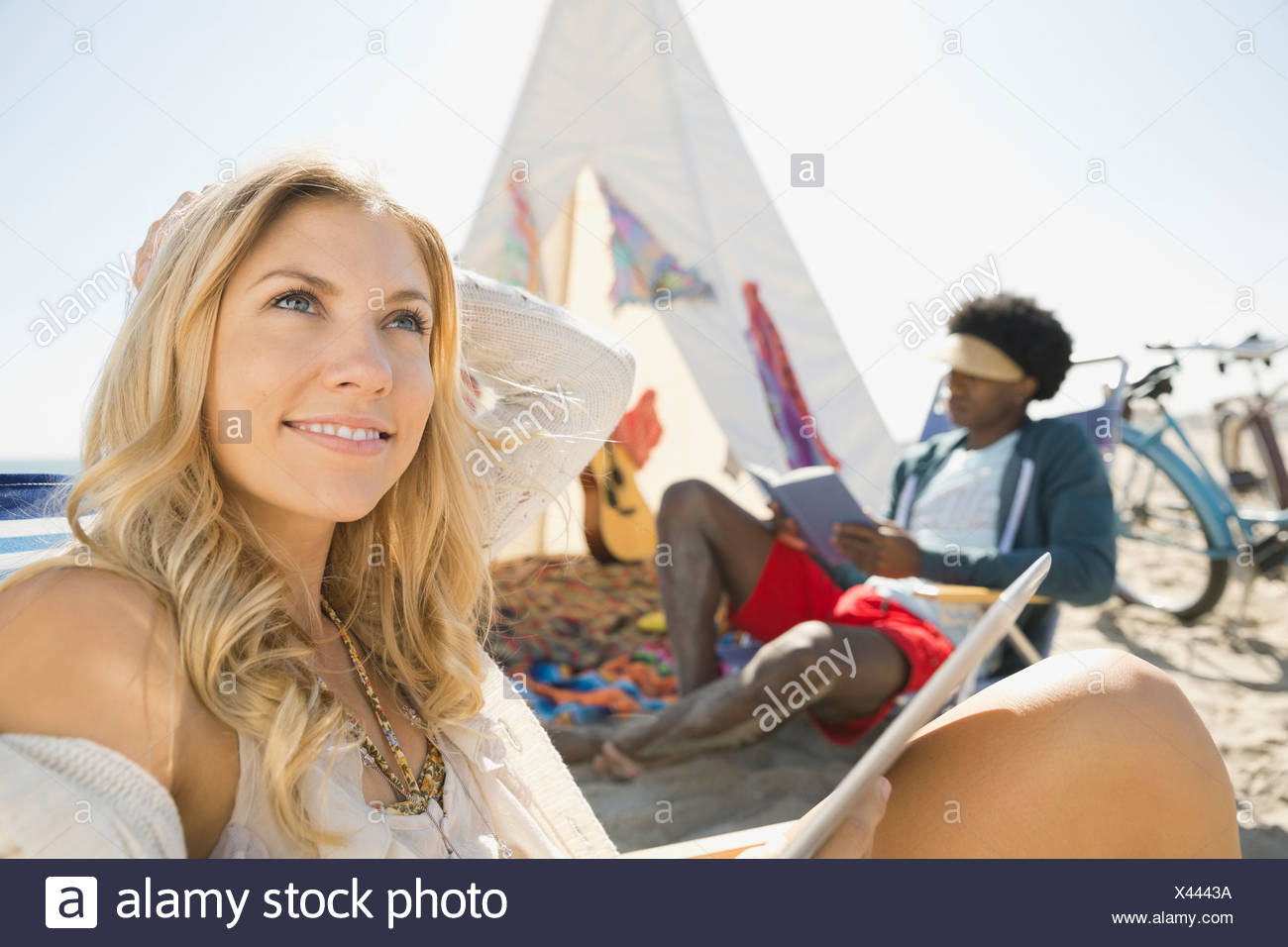 Thoughtful woman daydreaming on beach - Stock Image