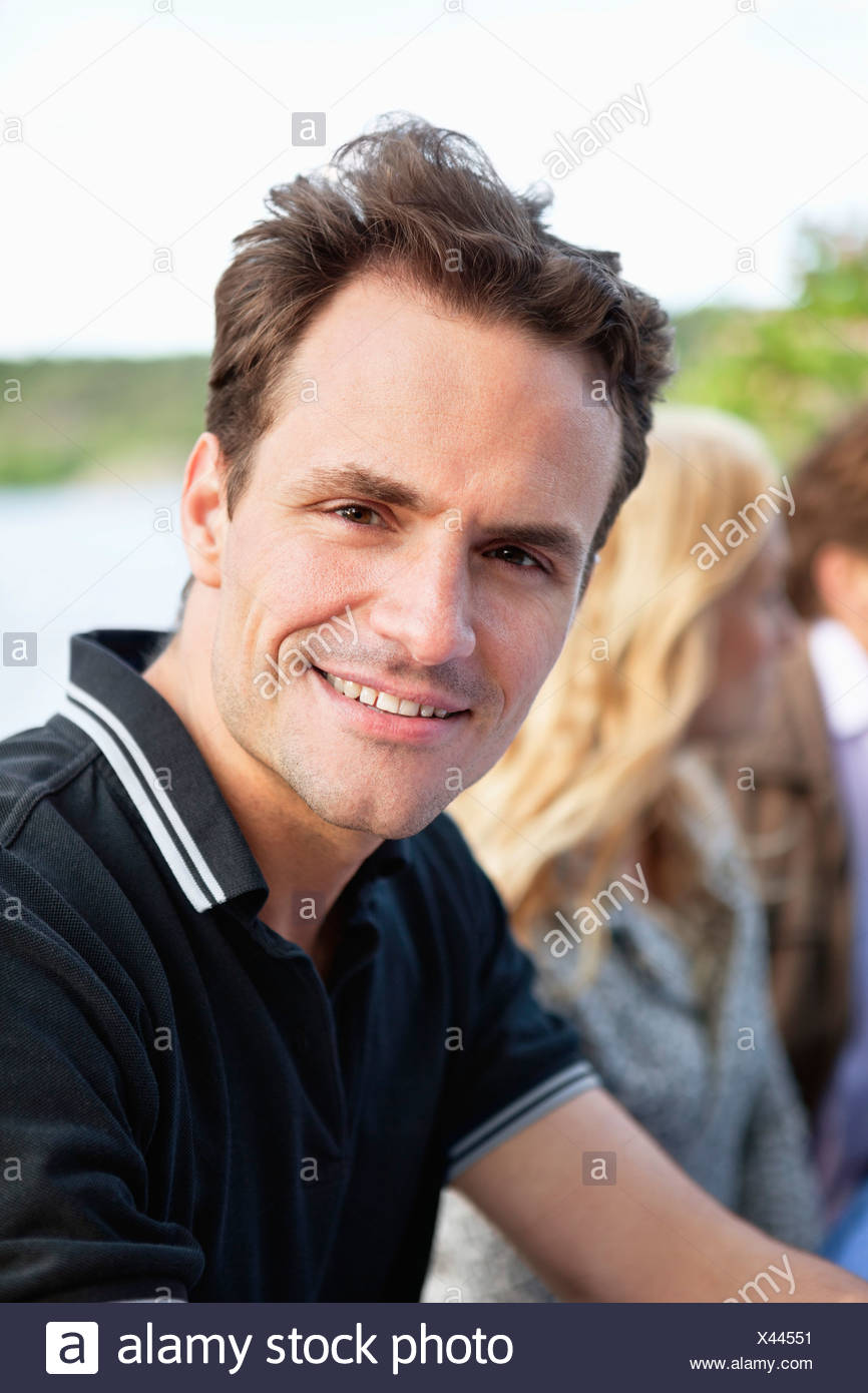 Portrait of man with friends in background - Stock Image