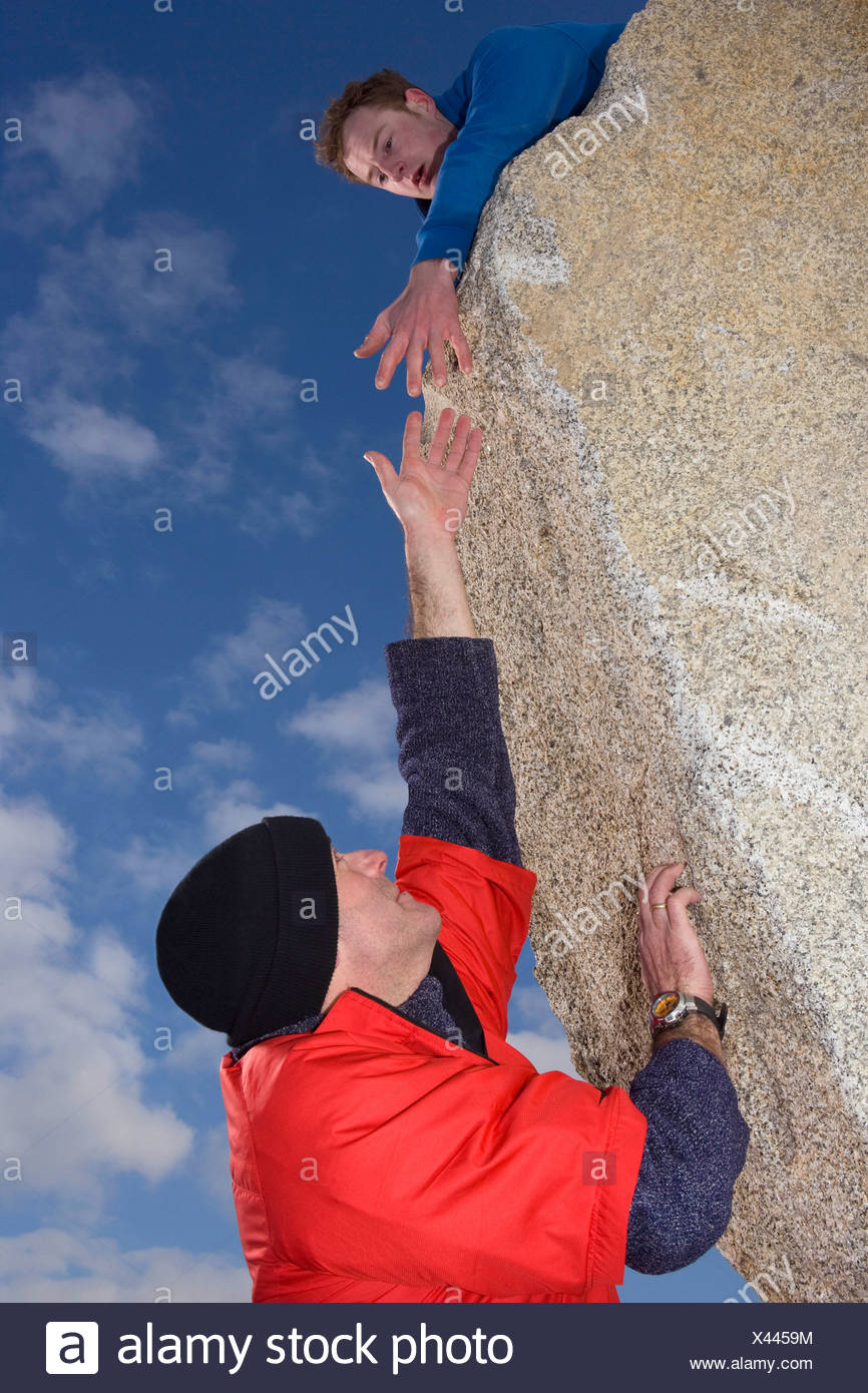 Climber offering hand to fellow climber Stock Photo