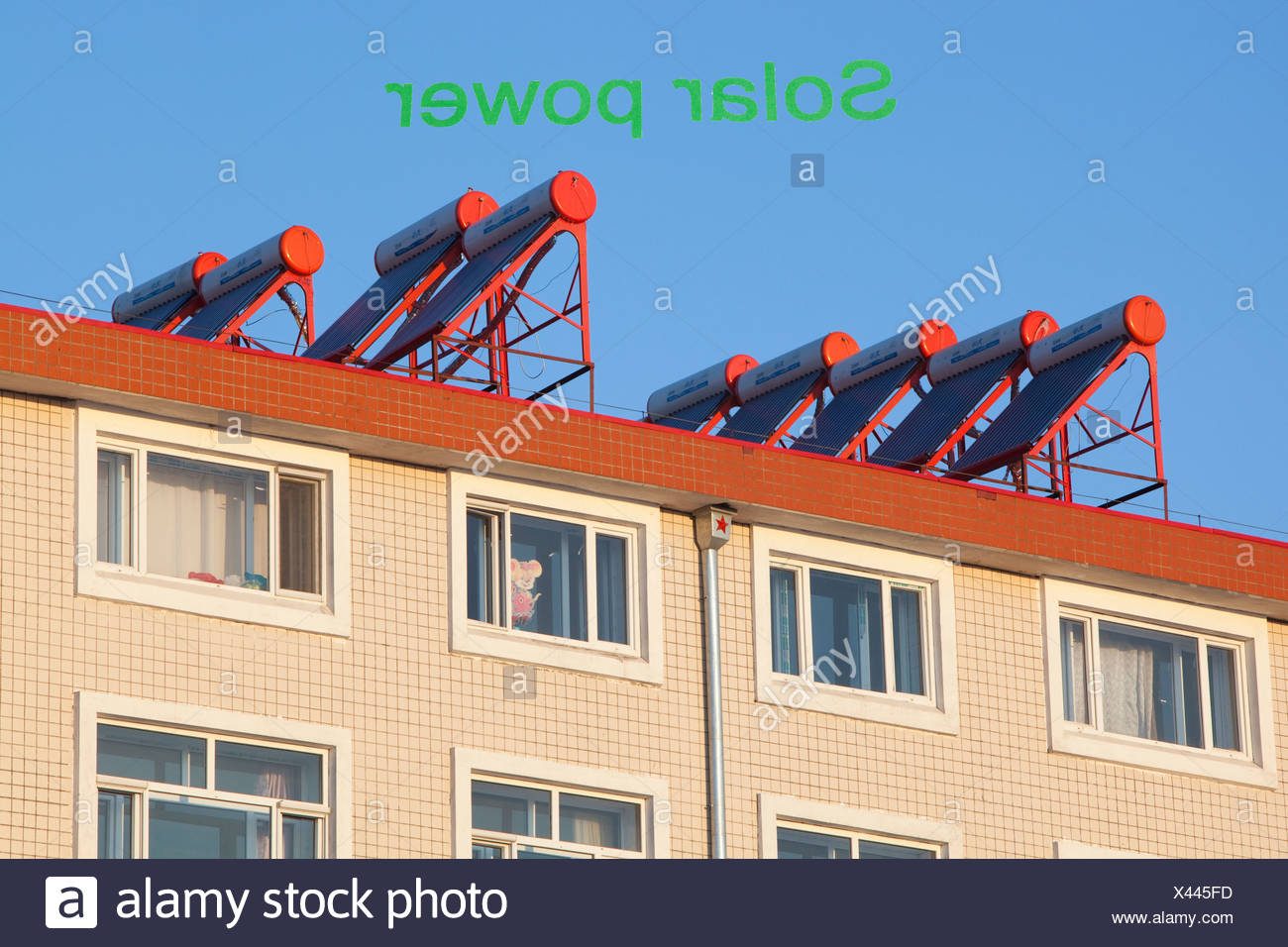Soalr water heaters on house roof in China. - Stock Image