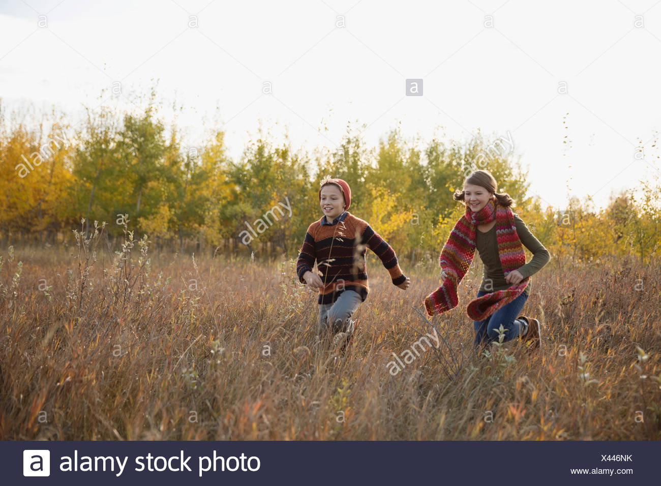Brother and sister running in autumn field - Stock Image