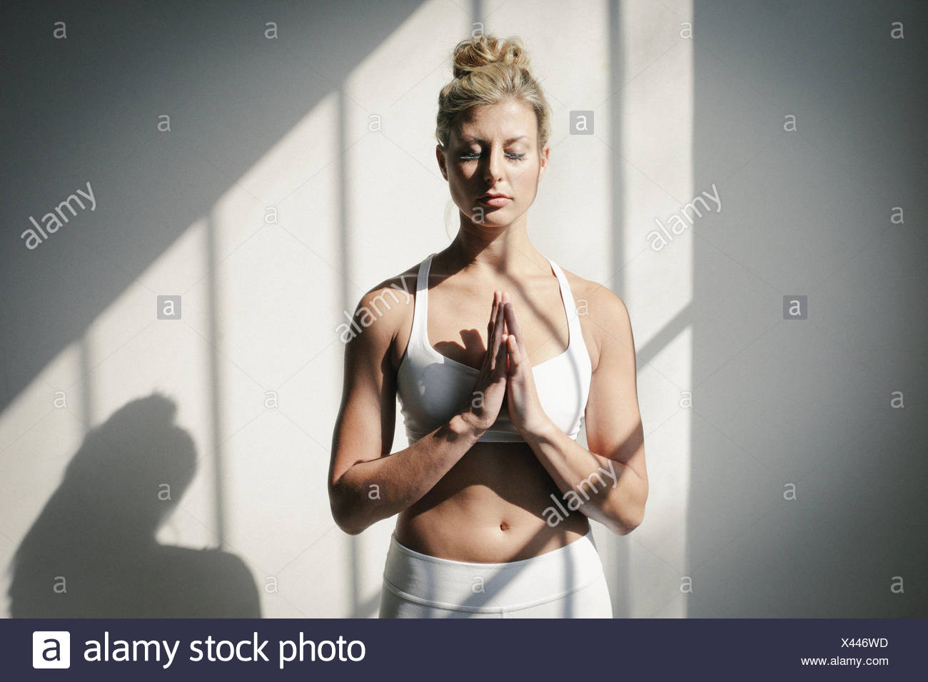 A blonde woman, her eyes closed, in a white crop top and leggings, standing in front of a white wall, doing yoga. - Stock Image