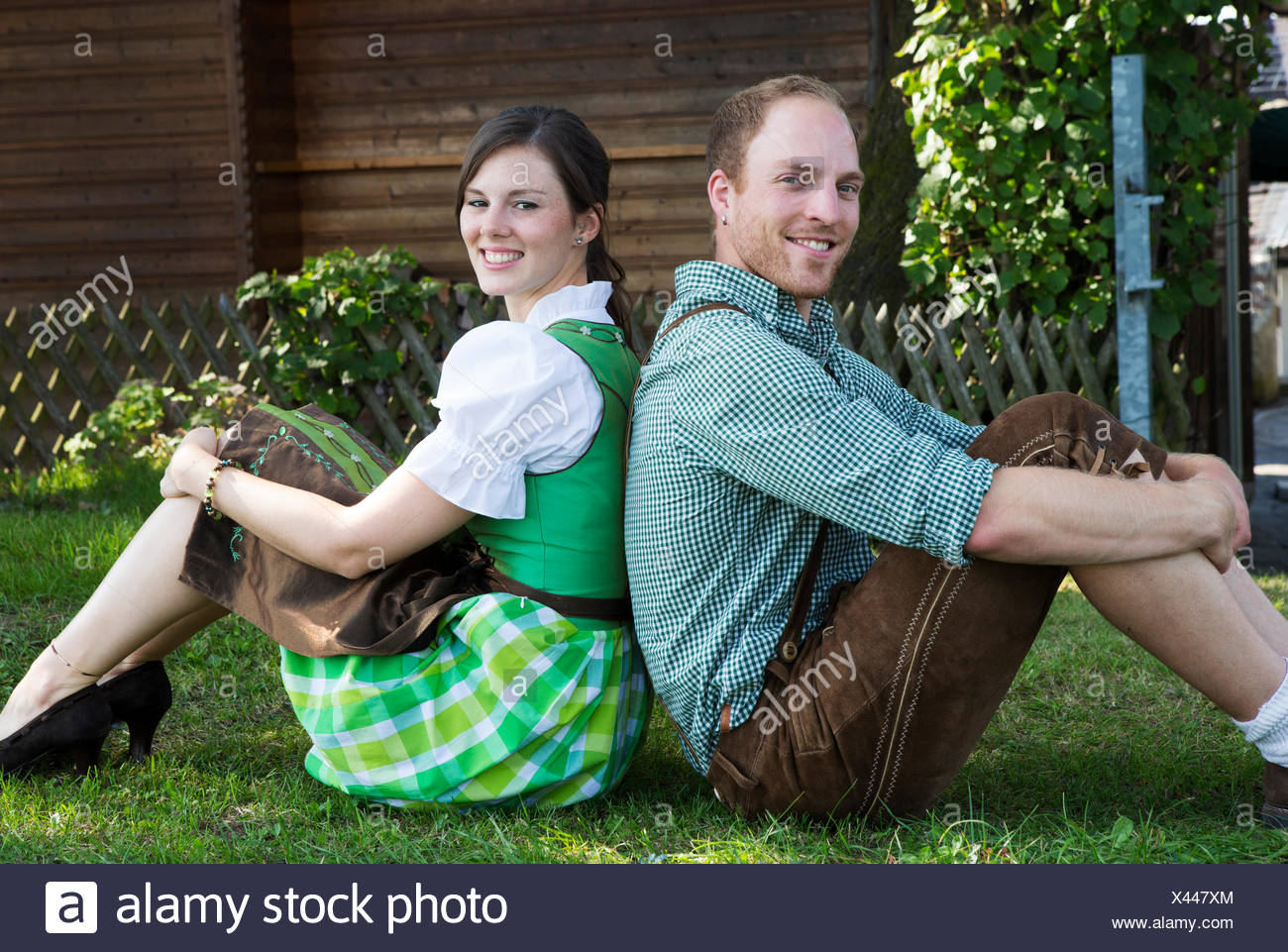 bavarian couple sitting in the grass - Stock Image