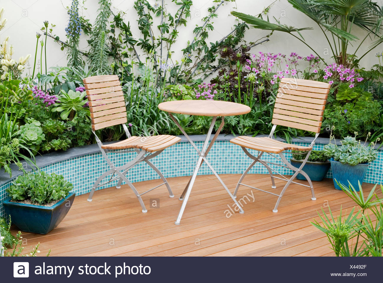TABLE & CHAIRS ON DECKING WITH CERAMIC TILE RAISED BORDERS BEHIND ...