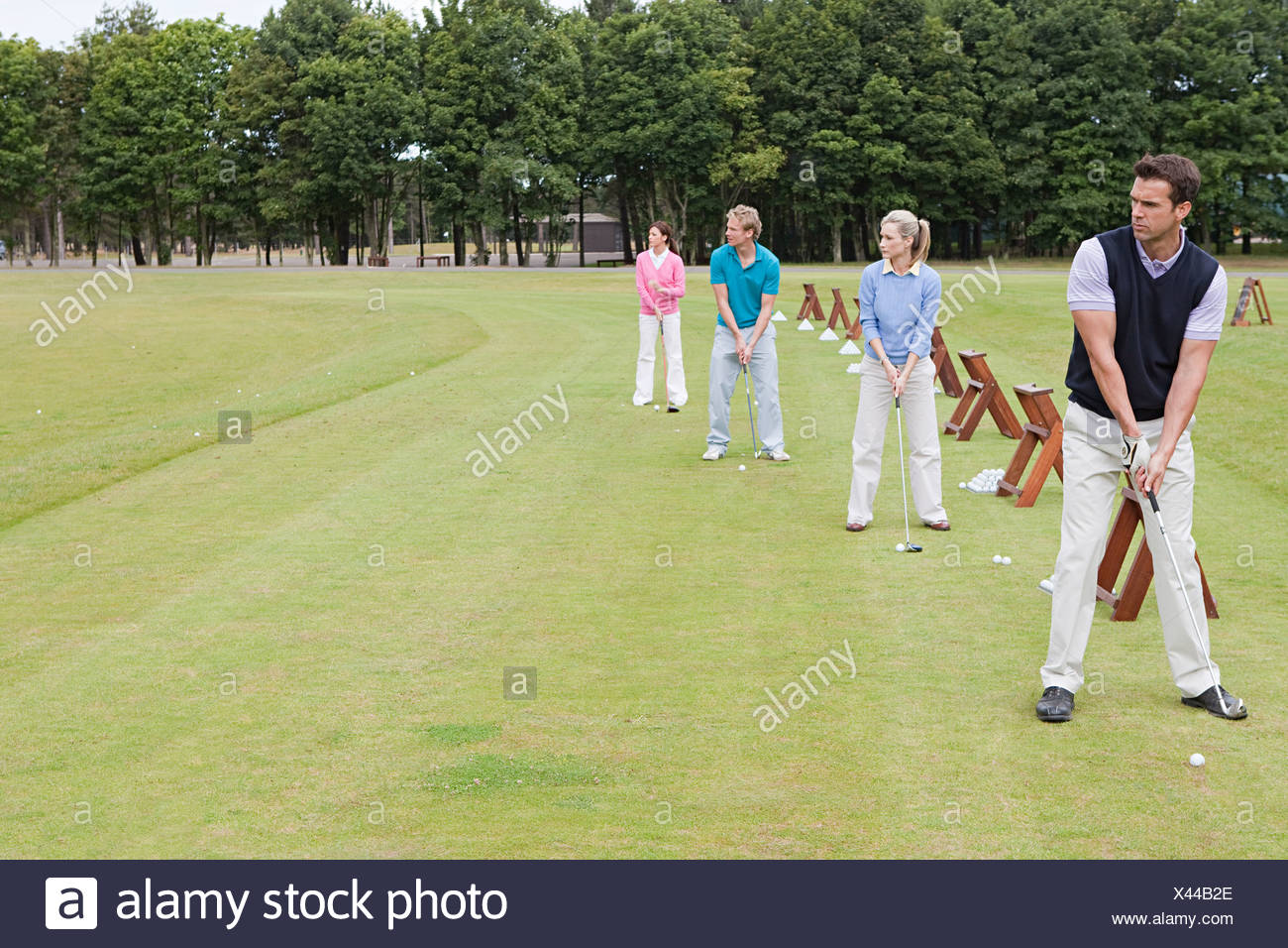 Four golfers on a driving range - Stock Image