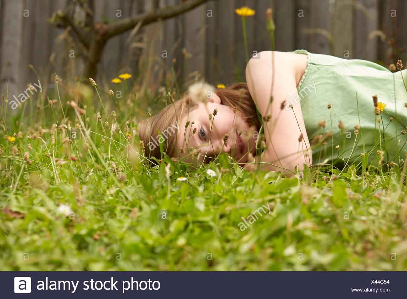 Girl lying on garden grass daydreaming - Stock Image