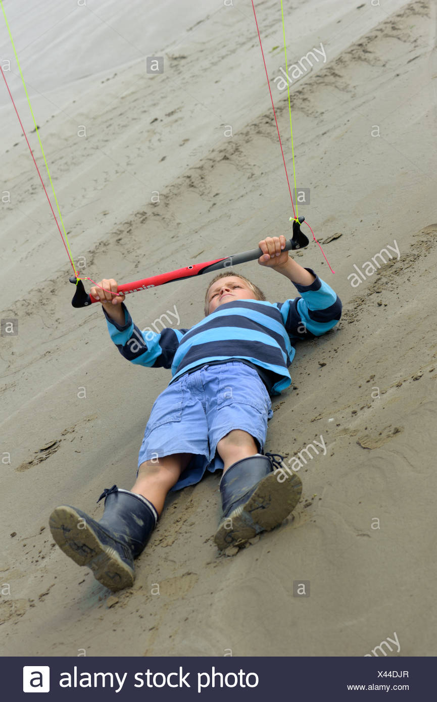 Boy flying a towing kite on the Atlantic beach, Finistere, Bretagne, Britanny, France, Europe, PublicGround - Stock Image