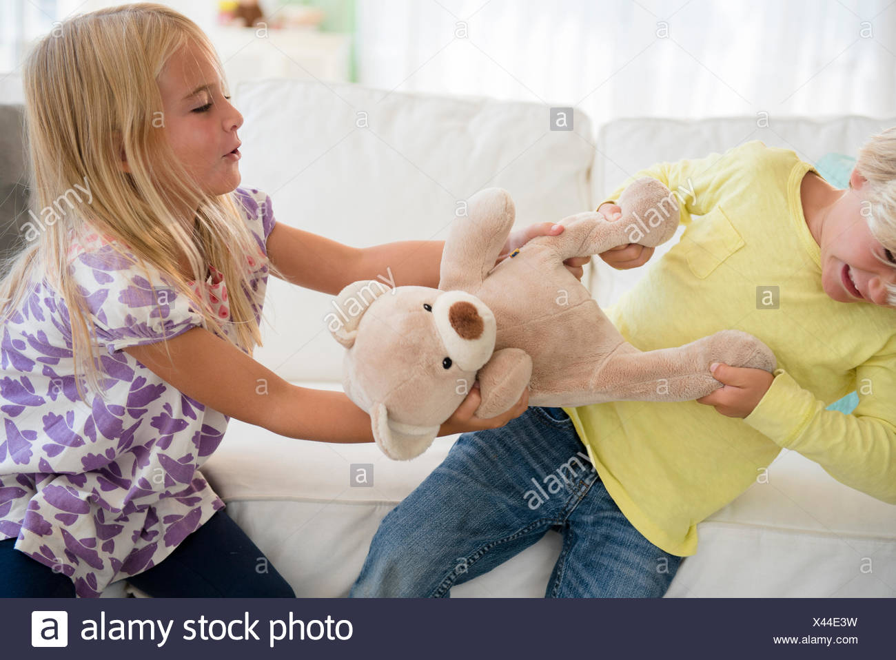 Boy (4-5) and girl (6-7) arguing - Stock Image