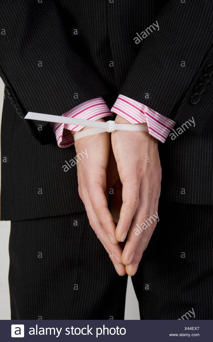 A businessman with his hands tied behind his back - Stock Image