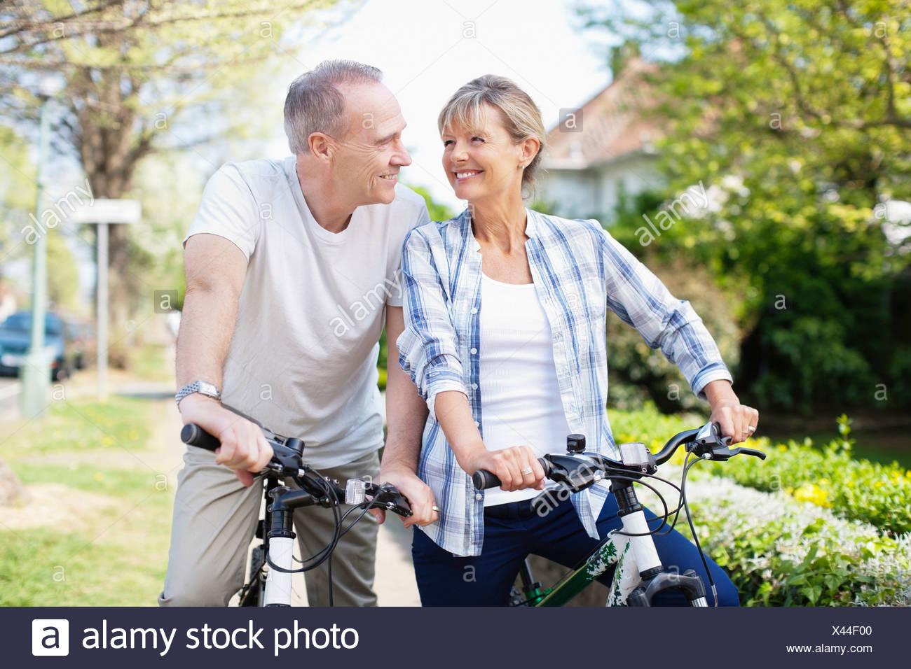 Senior couple riding bicycles - Stock Image