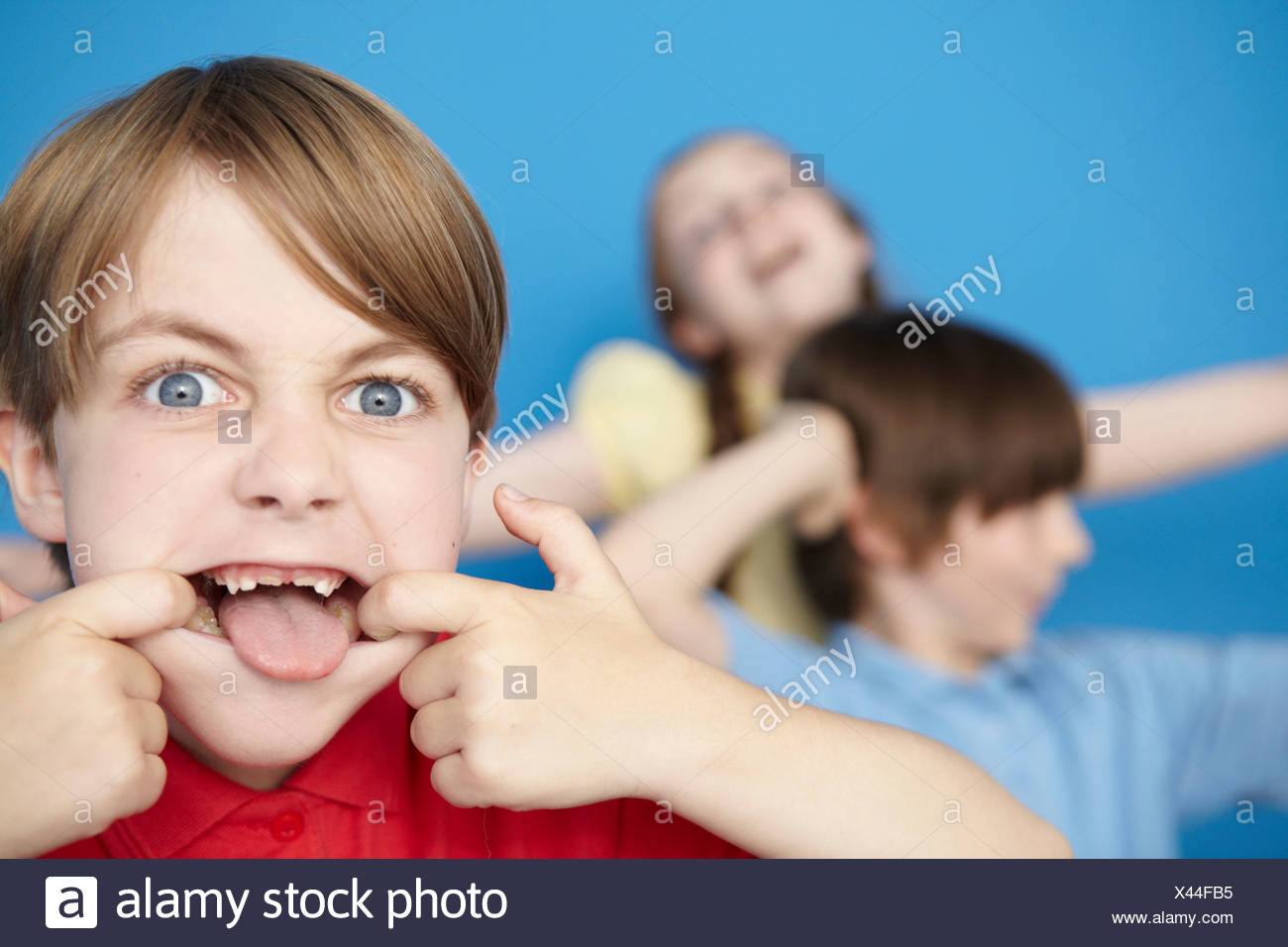 Portrait of boy sticking out tongue, blue background - Stock Image