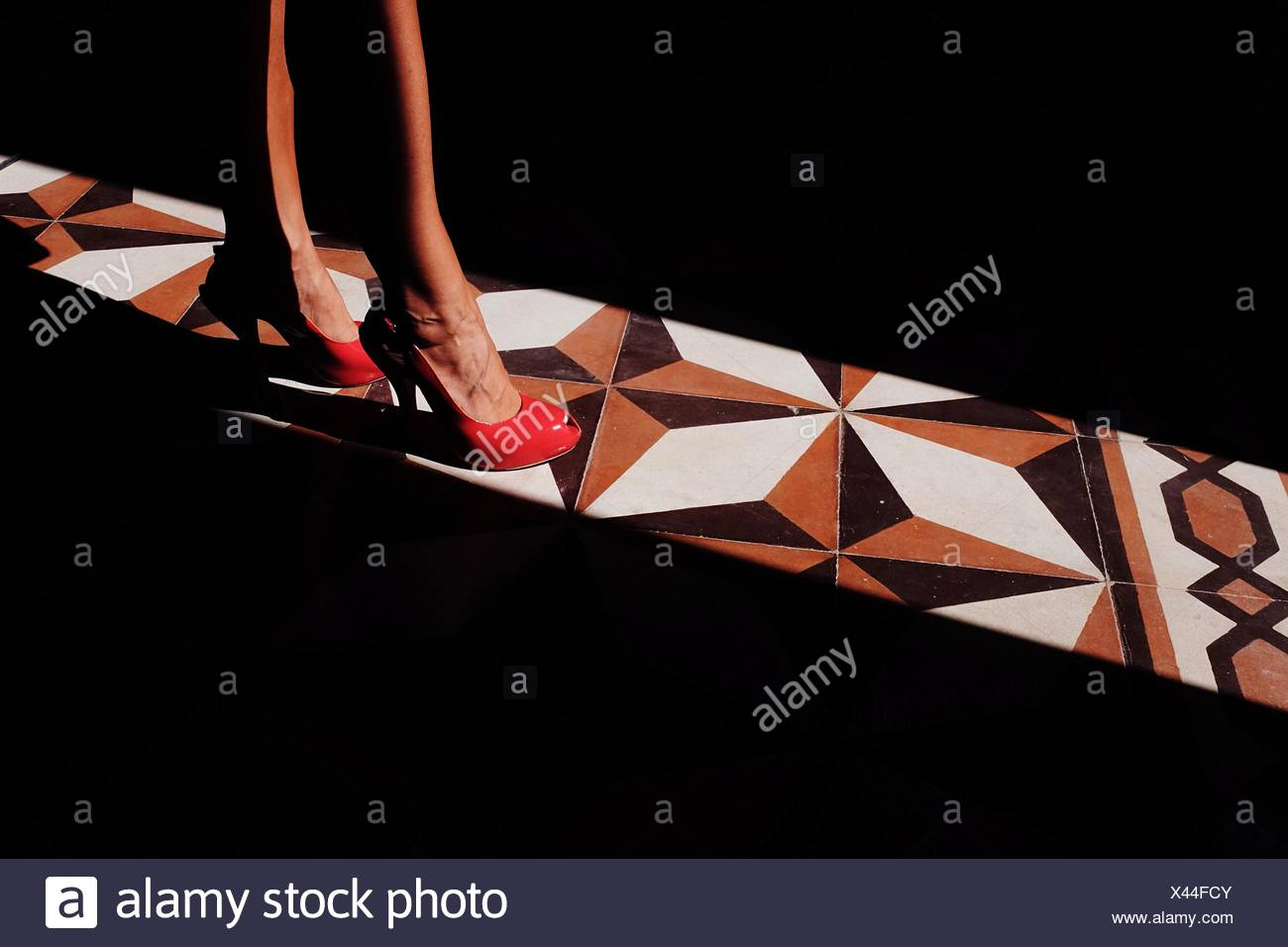 Low Section Of Woman Standing On Sunlight Over Tiled Floor - Stock Image
