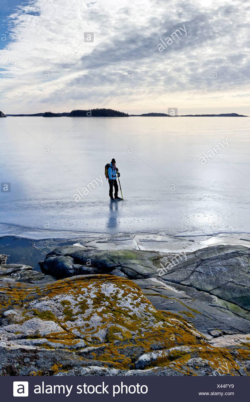 Person skating at frozen sea - Stock Image