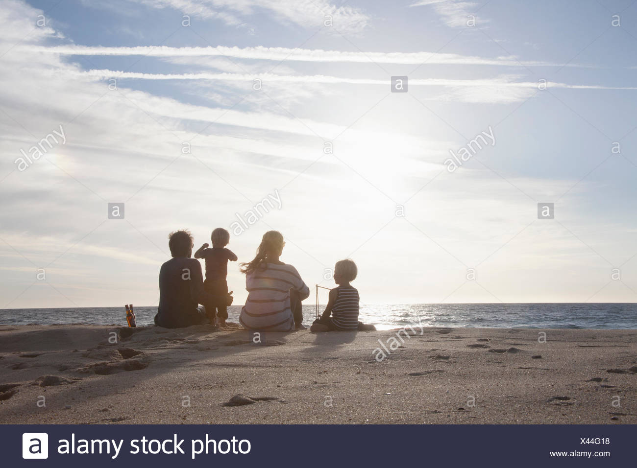 Back view of familiy with two kids sitting on the beach at twilight - Stock Image