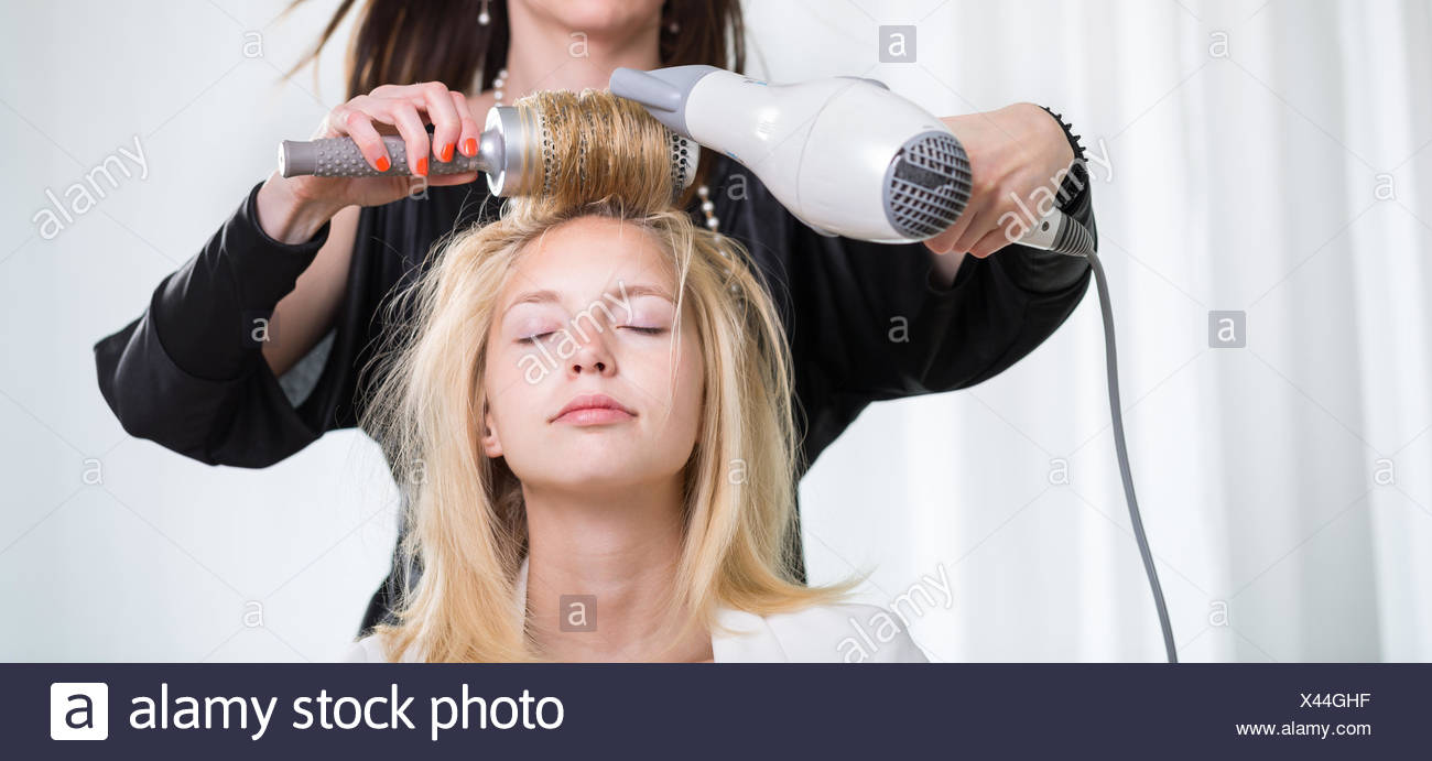 pretty young woman having her hair done by a professional hairstylist stock image