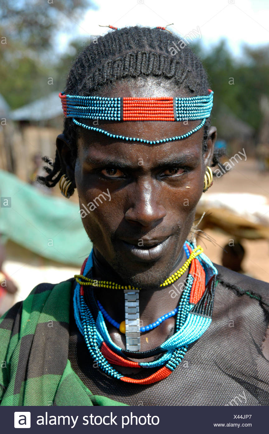 Man wearing a colorful bead headband and necklace, portrait, at the markets in Dimeka, Ethiopia, Africa - Stock Image