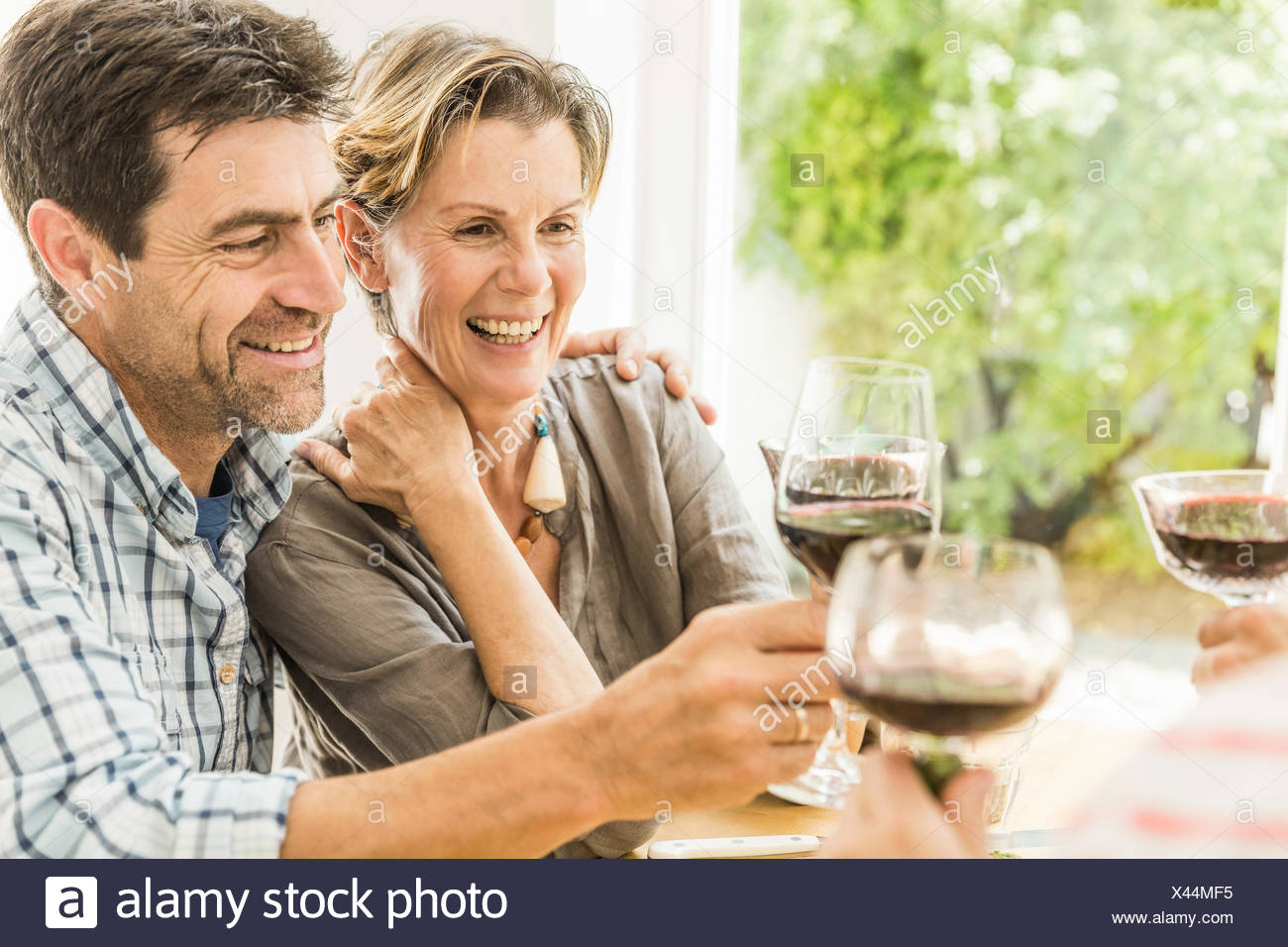 Couple toasting with red wine at dining table - Stock Image