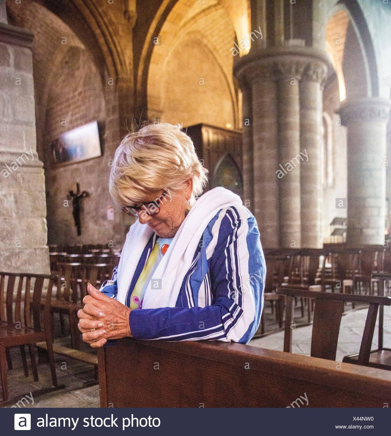 Older mature senior blond hair woman sitting at the pew and being very spiritual as she prays to god in a church in France. - Stock Image
