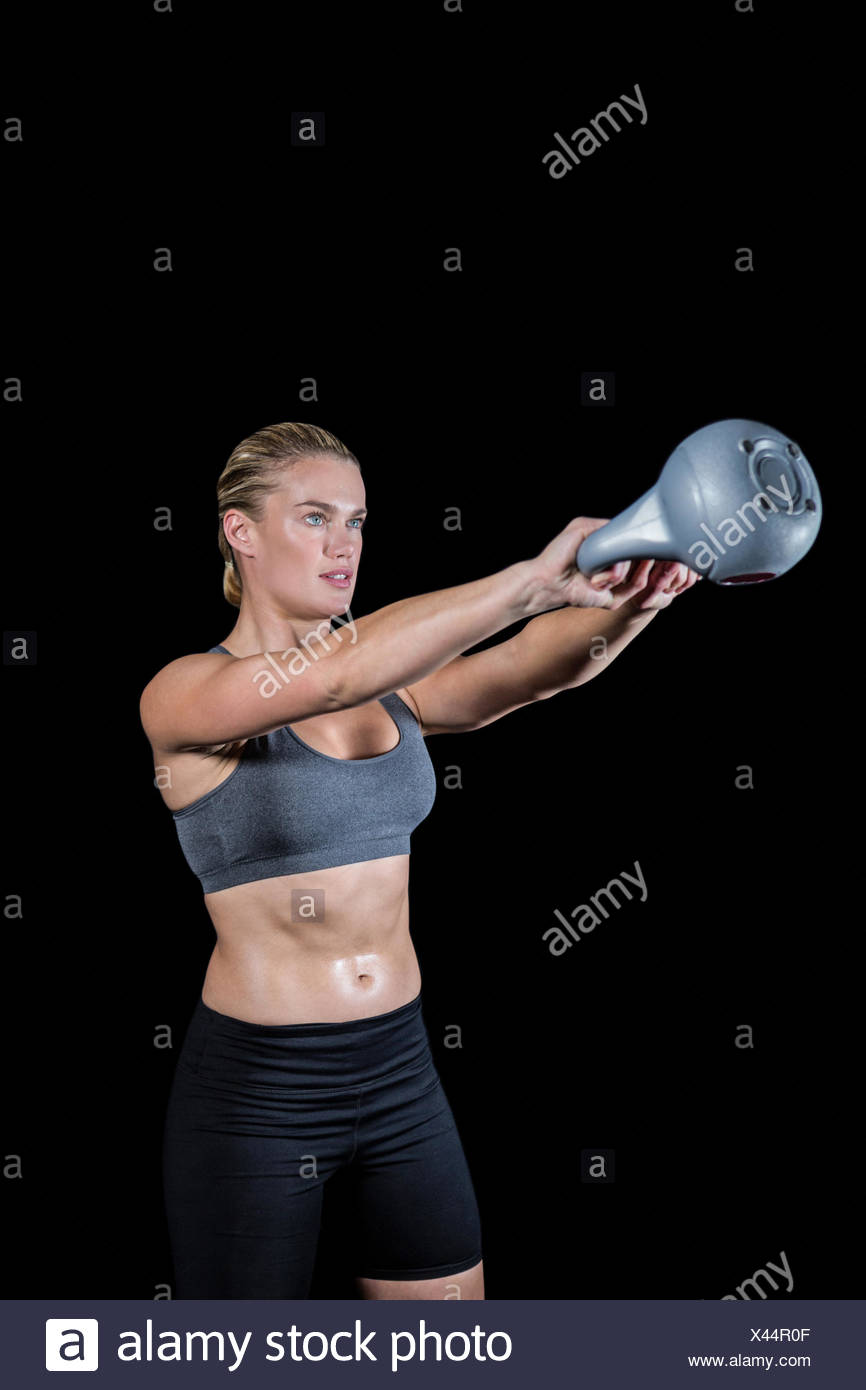 Muscular woman swinging heavy kettlebell Stock Photo