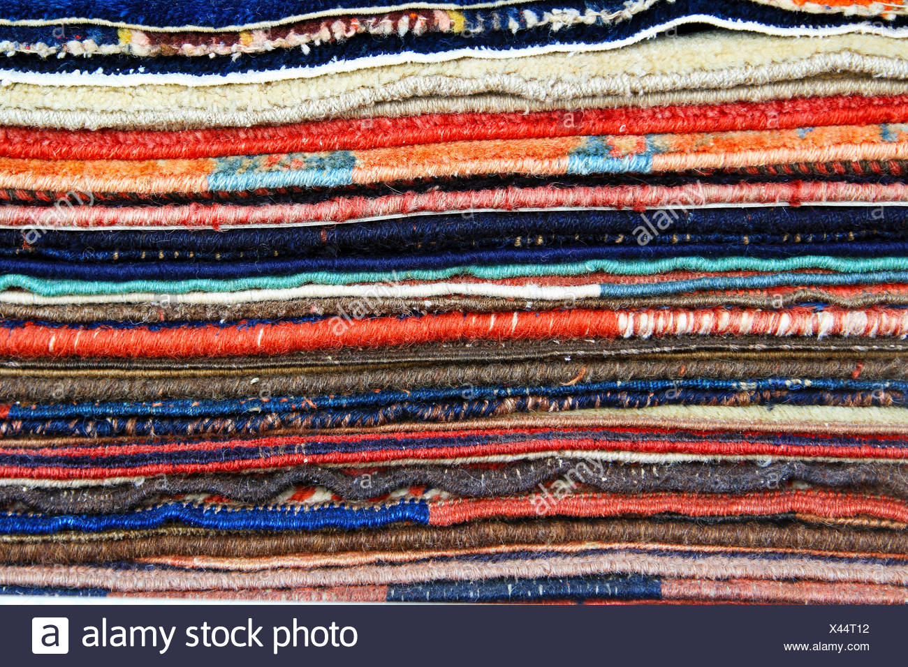 Big pile of colorful carpets and rugs - Stock Image