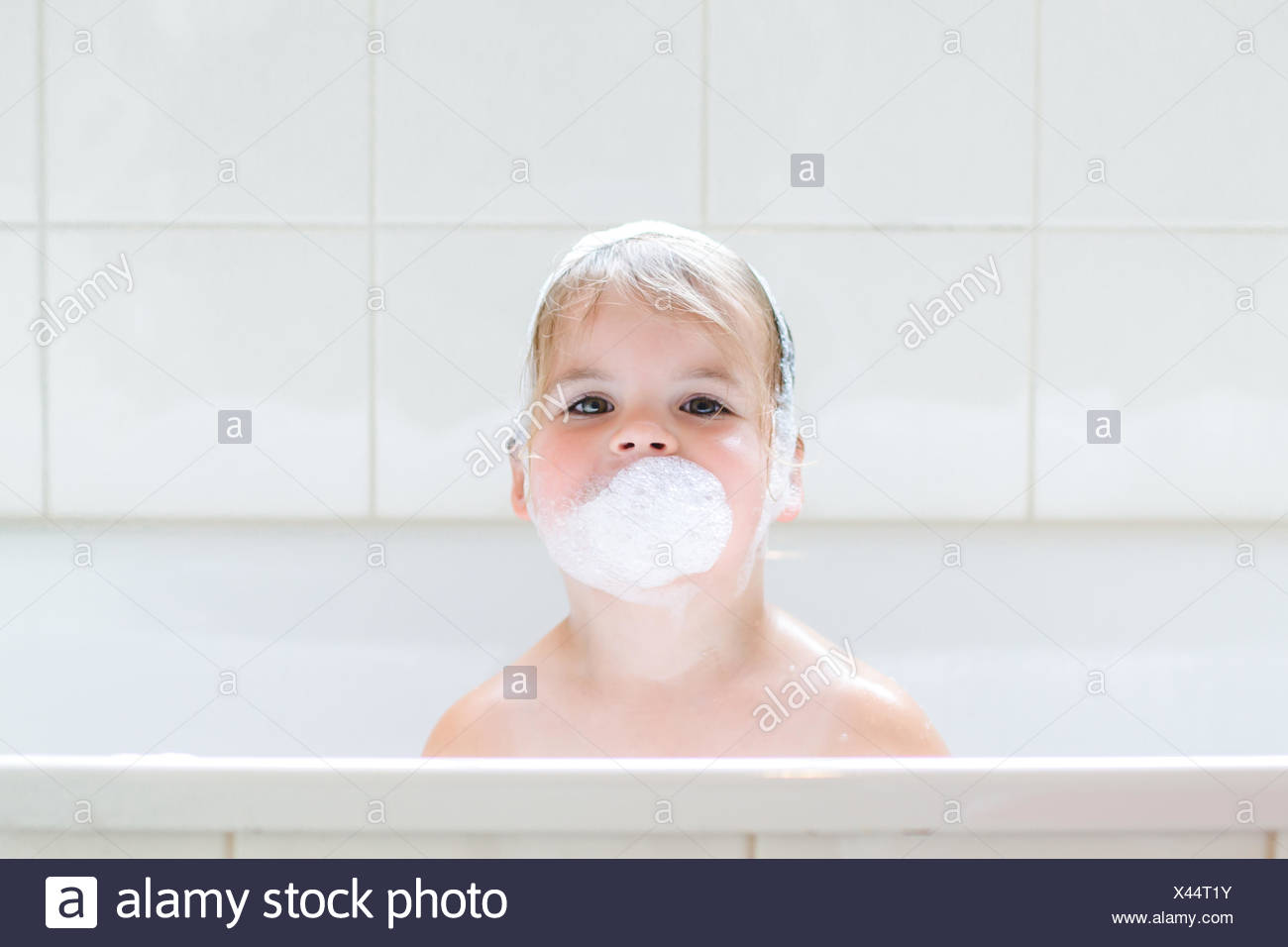 Girl in bath with bubble bath suds on face - Stock Image